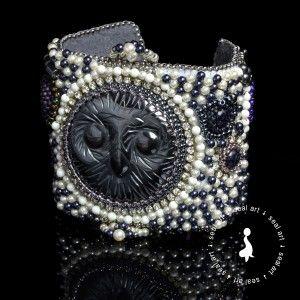 Efektowna bransoletka wykonana w technice Bead Embroidery. Element centralny stanowi piękny kaboszon z hematytu w kształcie sowiej głowy o średnicy 4,5 cm. Bransoletka wyszywana perłami Swarovski, ozdobiona kaboszonami szklanymi oraz kamieniami 'noc Kairu'. Dopełniona hematytem, taśmą cyrkoniową i koralikami Toho. Zapięcie w kolorze srebrnym. Idealny prezent na każdą okazję: urodziny, imieniny, walentynki, pod choinkę.