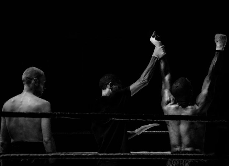 Winner looser. Black and white photo of a kick boxer, taken at an event in The Netherlands. The rederee decides who the winner is.