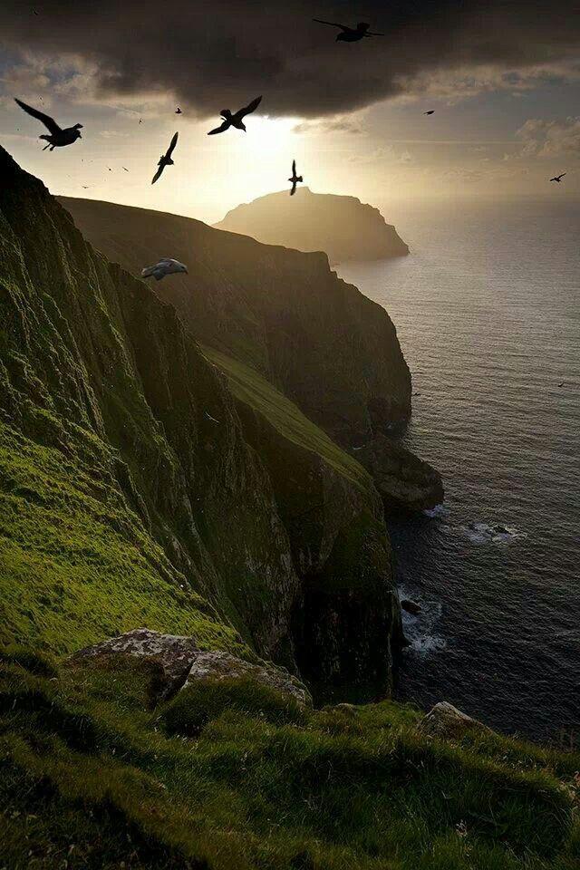 St.Kilda by Marcus McAdam, Scotland Grüne Felsküste am Meer, sehr dunkel, mit Licht hinter einer Wolkendecke - Schottland!