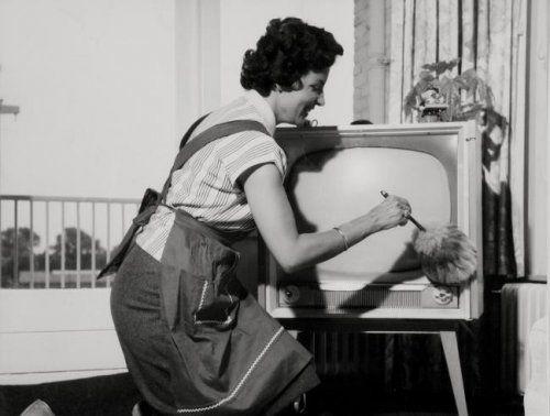 Een huisvrouw met schort aan, is met een plumeau bezig een televisietoestel van het stof te verlossen.