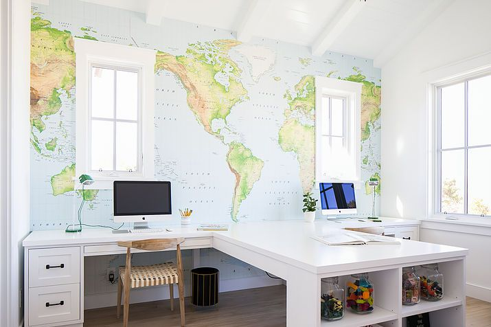 Fantastic kid's homework room features an accent wall lined with a world map mural lined with two built in desks paired with mid century modern chairs flanking a built in craft desk fitted with shelves.
