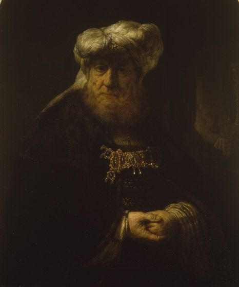 A man in oriental costume (King Uzziah stricken by leprosy) Oil on panel; circa 1639 Rembrandt van Rijn (1606 - 1669) Half-length figure of an old man, with his hands clenched in front of him, standing in a dark interior. He is wearing a white turban and fur-trimmed cloak, held at the chest by a large gold and jewelled clasp. The identification of the sitter has long been discussed, and has traditionally been described as a 'rabbi' or 'oriental'.