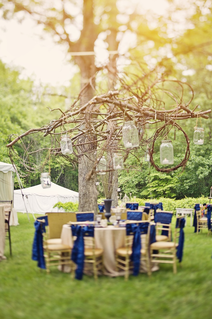 Stick/grapevine chandelier with hanging mason jar candles, suspended in air between trees. Outdoor reception. Gold/navy/pink reception. By Chelish Moore. www.chelishmoore.com. Photo by Connection Photography. www.connectionphoto.com.