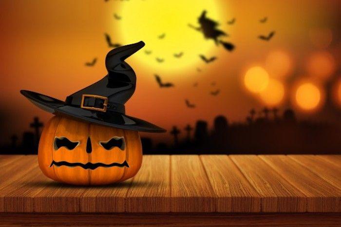 ein Kürbis mit Hexenhut   Halloween Hintergrund mit vielen Silhouetten