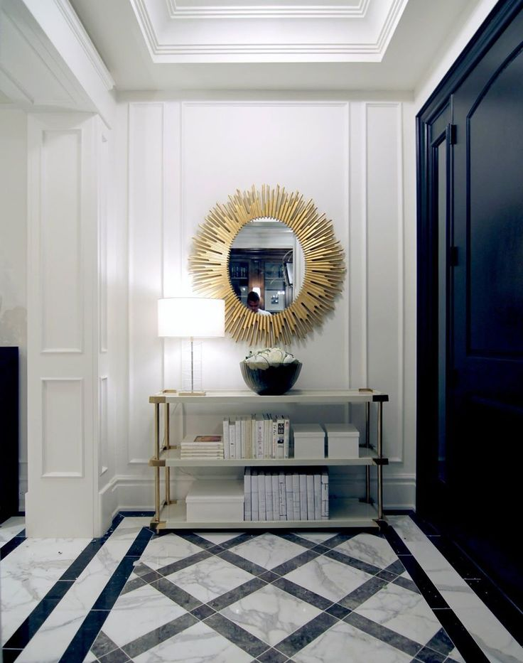 Entrance Hall with statement sunburst mirror and marble tiles featuring a lattice pattern.