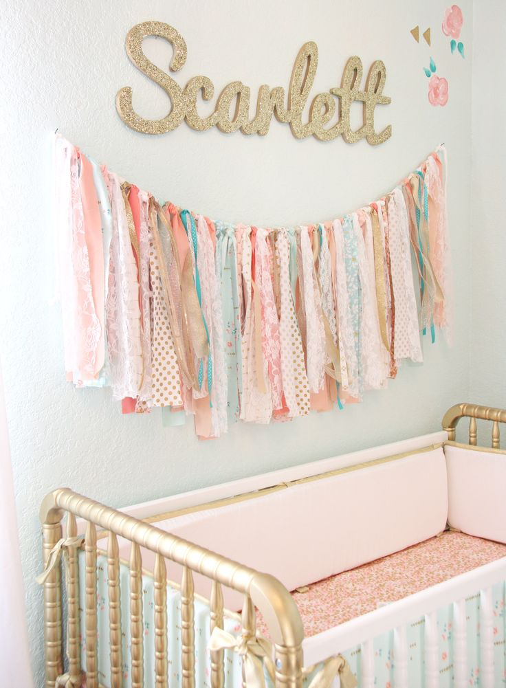 fabric banner and glittered custom name wall decor above the crib