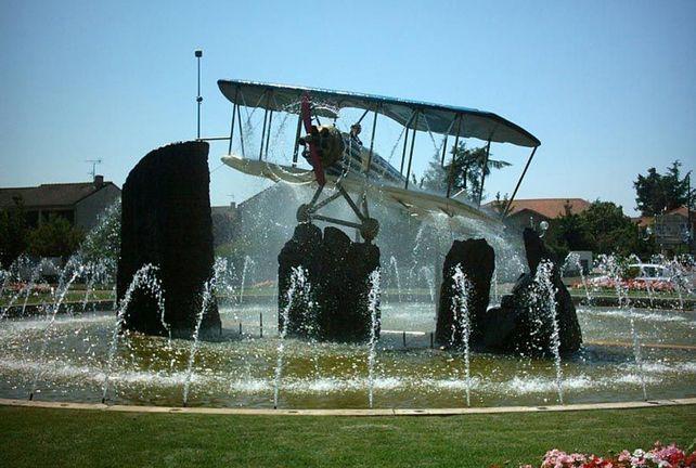 Deux paires d'ailes, 20 mètres de diamètre... Cet avion grandeur nature en résine sculpté par Rémi Coudrain en 1995 rend hommage aux premiers biplans fabriqués dans les usines Bouthéon. Le mouvement de son hélice ? Animé par la pression de l'eau de la fontaine.Par B. Monier-Vinard et J. Saint-Medar © DR