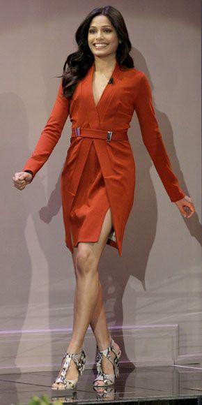 Freida Pinto in a beautiful, rust Marios Schwab wrap dress and python sandals.