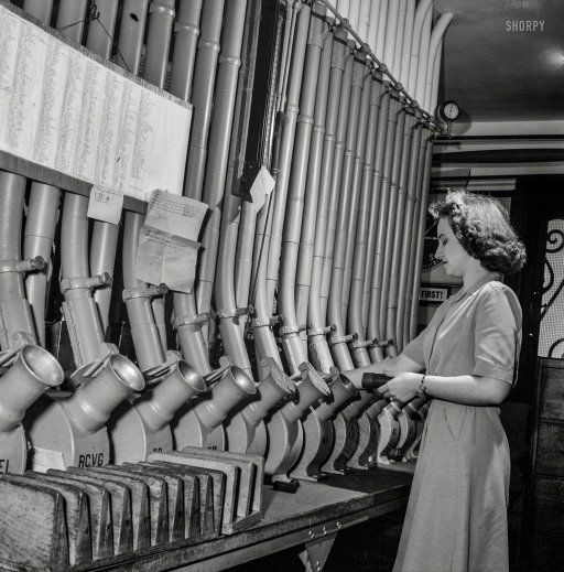 """June 1943. Washington, D.C. """"Miss Helen Ringwald, employee at the Western Union telegraph office, works with the pneumatic tubes through which messages are sent to branches in other parts of the city for delivery"""