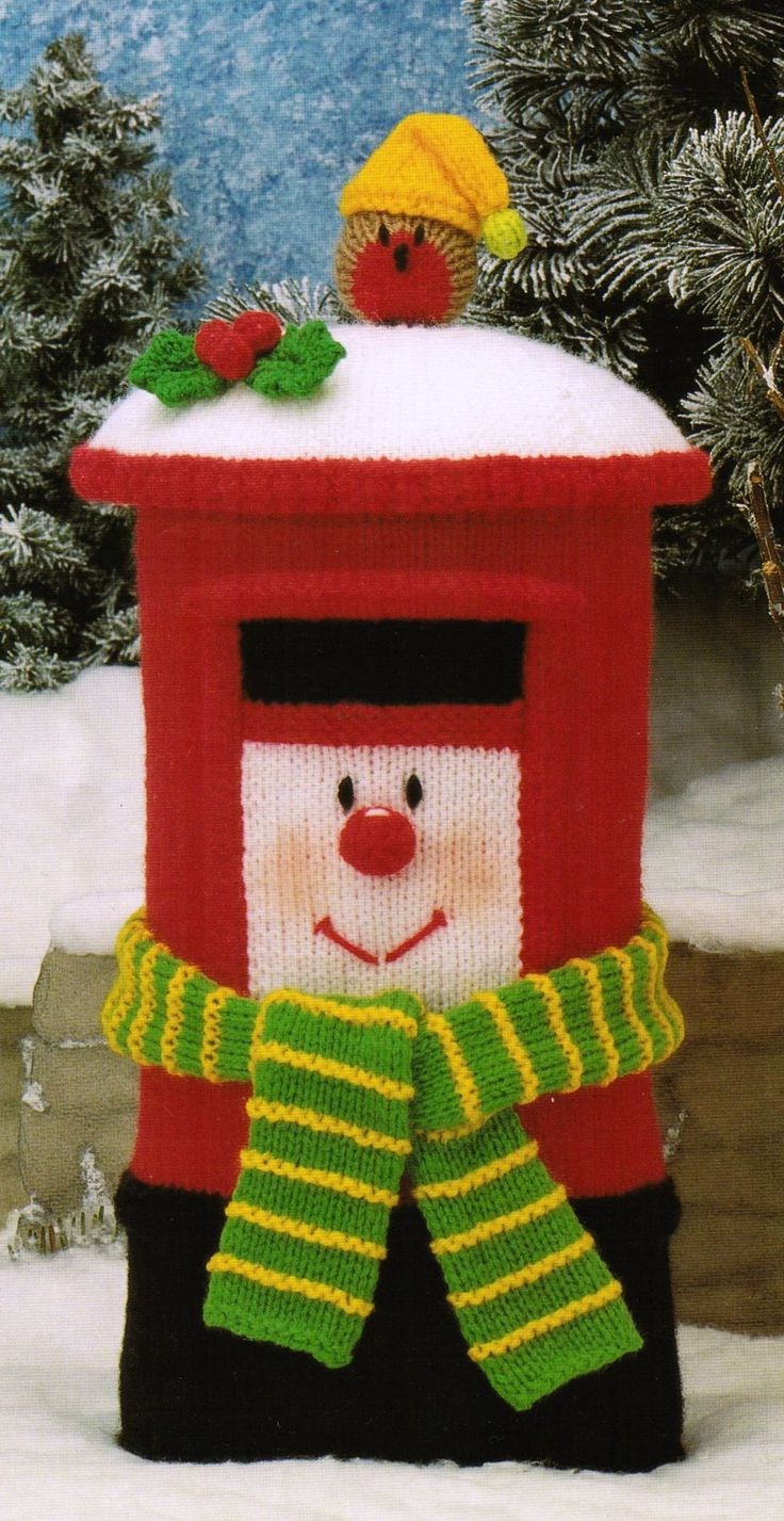 """From 'Celebration Clowns', Pt.2 of Jean Greenhowe's 'Red Nose Gang' collection the fabulous Clarence the Christmas Postbox. Knitted with DK wool, covered in snow and standing 30cm/12"""" tall he is all set to deal with the flood of Christmas cards that is coming! How can he not bring some winter cheer? Designed and published by Jean Greenhowe Designs in 1993."""