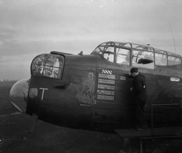 LAC E Turner paints the 65th 'raid completed' symbol onto the nose of an Avro Lancaster B Mark III