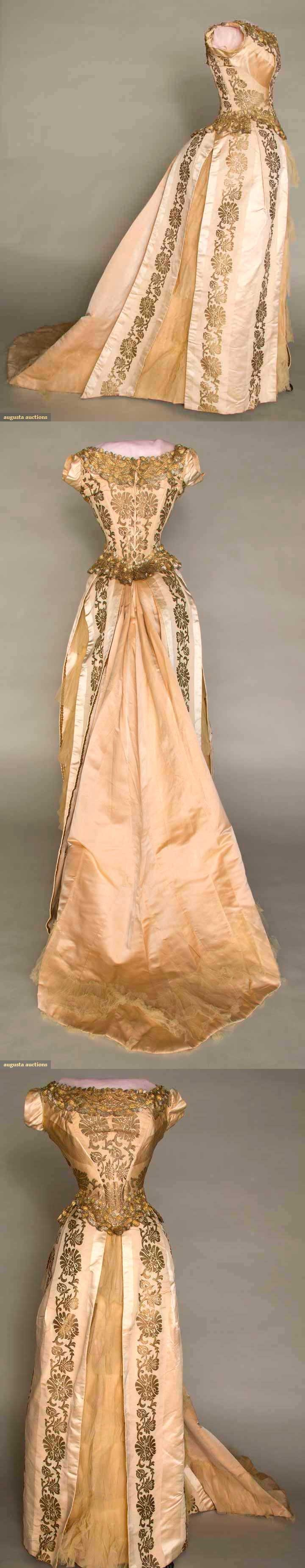 1880-1885 two-piece gold brocade ballgown with alternating faille and wide satin cream silk stripes. Heavy gold and silver metallic bobbin lace trim on back-lacing bodice, beige satin skirt train with tulle flounce. Skirt with three sections of pleated tulle between silk panels.