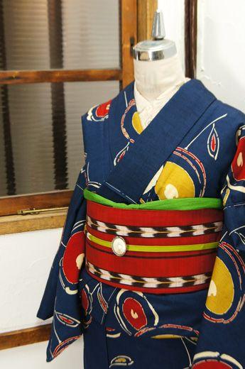 紺青色の地に、ころんと丸い光琳菊をアレンジしたようなお花模様が染め出された胴抜き仕立てのウール着物です。