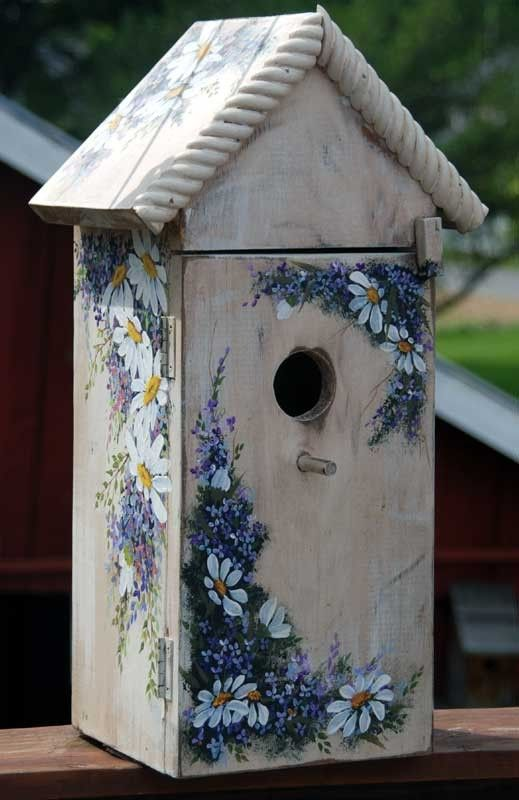 This birdhouse is decorated with hand painted blue and purple flowers and daisies.  The decoration looks beautiful against the plain wood.