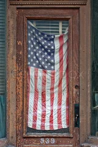 Old American flag behind an old door
