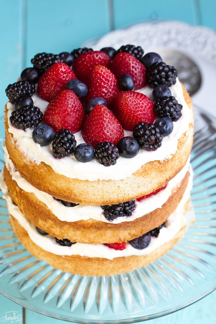 Easy Berries and Cream Sponge Cake layers with the best fluffy whipped cream, fresh strawberries, blueberries & blackberries. Perfect for any party.