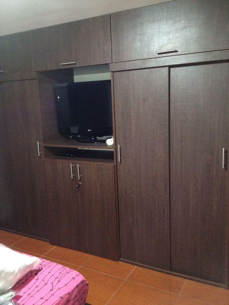 Closet de tres cuerpos color caoba con puertas corredizas for Closet con espacio para tv