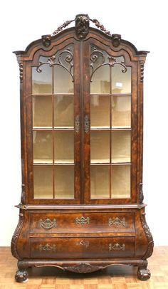 Een wortelnotenhouten vitrinekast  met twee deuren. In de onderkast twee gebogen laden, de kuif met snijwerk en op klauwpoten 19e eeuw Opbrengst: € 200,00