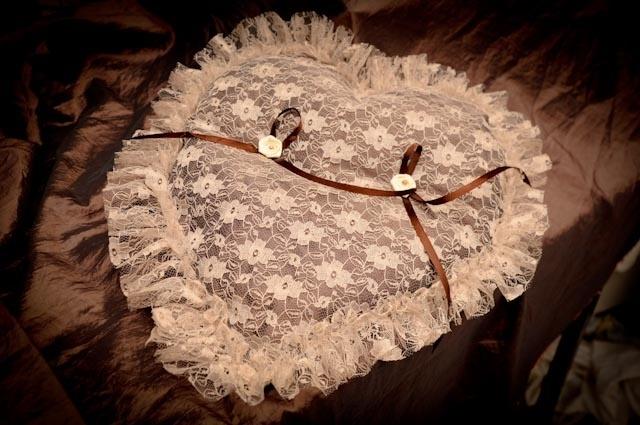 Grand coussin de mariage en dentelle fond de taffetas chocolat et dentelle champage avec 2 noeuds de ruban de satin chocolas pour attacher les alliances et 2 roses crème avec perle de culture champagne - 38 cm de large x 38 cm en forme de coeur -  Matériaux utilisés : Dentelle Taffetas