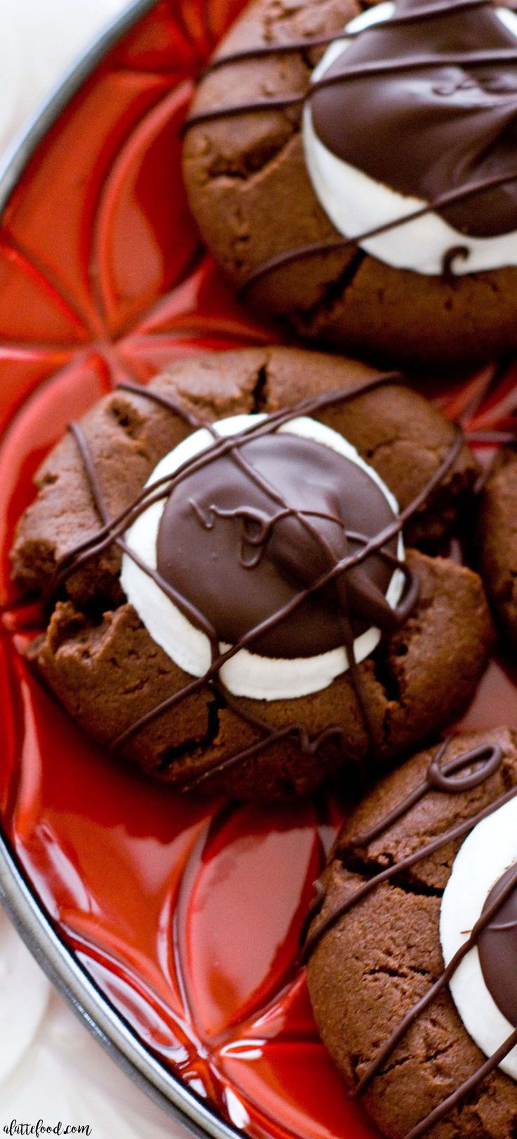 These Hot Chocolate Thumbprint Cookies taste like homemade hot chocolate in the form of a chewy chocolate cookie! They're intensely chocolatey, have a gooey marshmallow center, and covered in drizzled chocolate. Perfect.#hotchocolate #cookie #dessert #christmas #thanksgiving