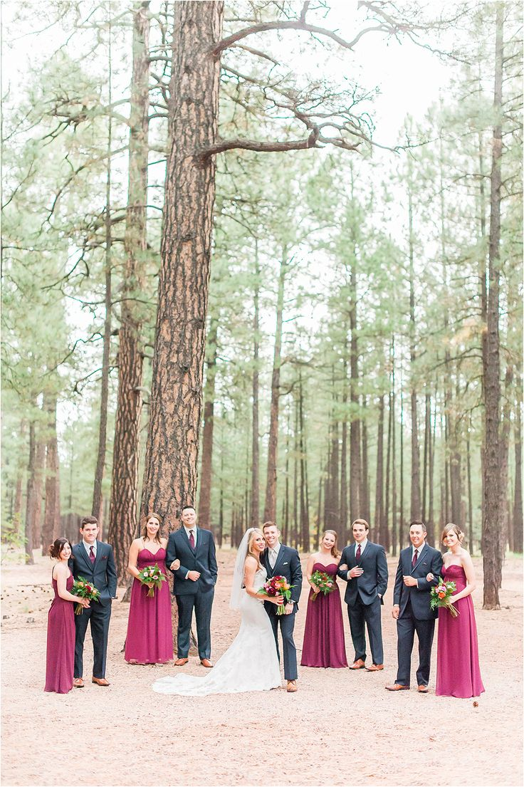 A rustic fall wedding in Pinetop Arizona at the Gathering Place wedding venue. The bride wore a lace sheath wedding dress with simple veil and the groom wore a navy suit. The wedding day was adorned with pink and cranberry ranunculus and deep cranberry bridesmaid dresses. The groomsmen wore navy suits with deep red ties for a more formal look - Photos by Drew Brashler Photography