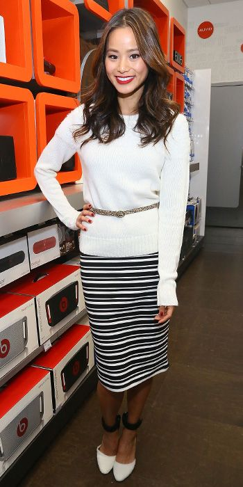 JAMIE CHUNG Chung attended the Charlotte Ronson Holiday Party in a white sweater that she belted over a striped pencil skirt. Two-toned ankle-strap heels completed her look.