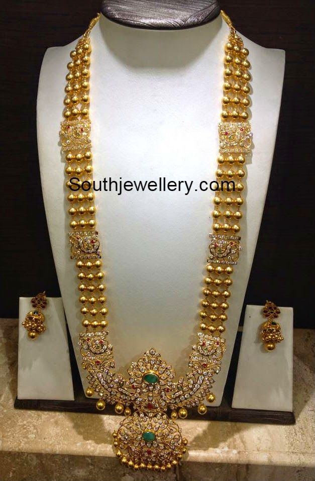 22 carat gold gundla haram with beautiful peacock design stones pendant studded with cz stones, rubies and emeralds. Weight: 110 grams For inquiries contact on Whatsapp: +91 97 00 009000 or Email: dharmesh25@yahoo.com Related Posts72 Grams Gundla Mala with Pachi PendantKundan Long HaramUncut Gold Balls Necklace and Haram Set85 Grams Chandraharam with Side PendantsAntique Gold