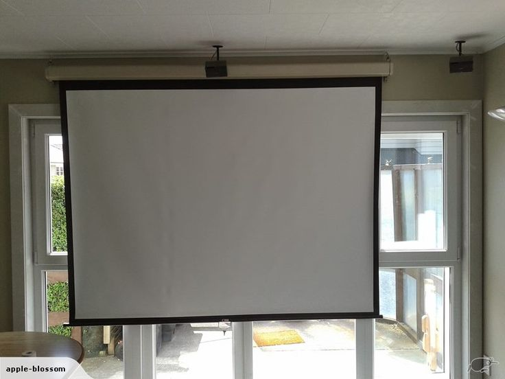 large projector screen hangs from ceiling via supplied hooks and secures to wall