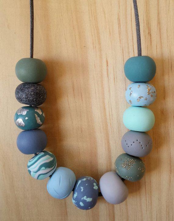 Ce collier est composé de 13 perles en argile polymère roulées à la main dans de belles nuances de vert et de pierre bleue avec des reflets argent.  Les perles sont enfilées sur un cordon en coton ciré noir d'excellente qualité et finis dans un noeud coulissant réglable qui permet à l'utilisateur de modifier la longueur du collier en fonction de leur style et leur tenue.  Le collier est composé d'un tableau de perles avec différents «embellissements», y compris: marbre, textures, feuille…