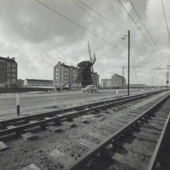 1950's. A view of the Haarlemmerweg in Amsterdam. De Haarlemmerweg is a road in Amsterdam which runs from the Nassaukade via Halfweg to the city Haarlem. In the background is the mill 1200 Roe. This mill is an eight-sided grondzeiler mill built in 1632 to regulate the water flow in the Osdorper Binnenpolder. The excess water was pumped in the Haarlemmertrekvaart which runs along-side the Haarlemmerweg. Photo MAI Beeldbank. #amsterdam #1950 #Haarlemmerweg