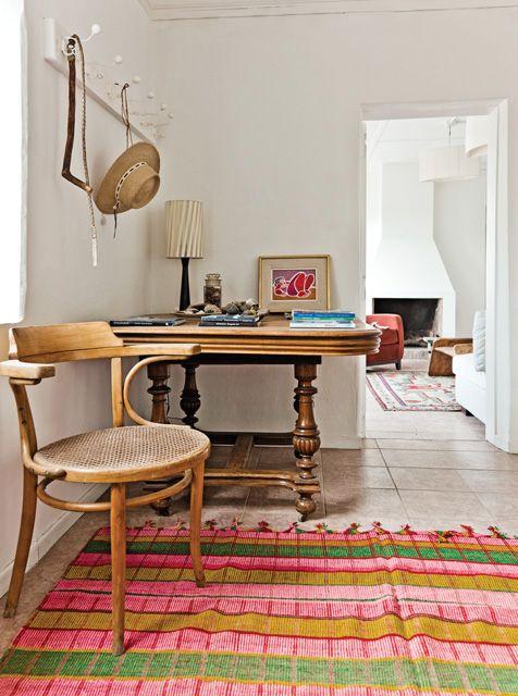 Rincón especial en la cocina de una casa patagónica con silla Thonet , mesa inglesa de madera, tapete colorido y perchero.
