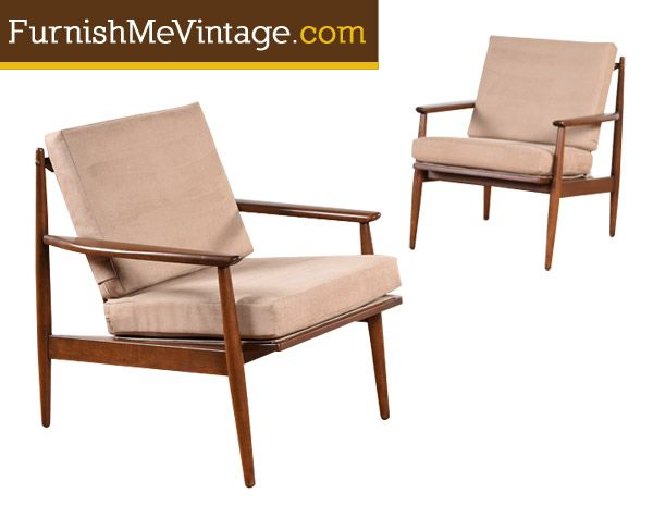 Handsomely restored pair of mid century modern arm chairs. The chairs are American made, vintage 1950s. The solid walnut wood frames are beautifully crafted with angular forms striking a sculptural silhouette. The back side is just as lovely with sleek spindles providing support.