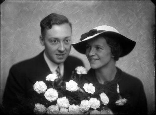 van den Berg | Studio-opnames. Een bruidspaar, de bruidegom in een zwart pak en de bruid eveneens in het zwart met breedgerande witte hoed met zwarte binnenkant, zwart lint  en een groot bruidsboeket van witte rozen.  Duvasel gravure. Haarlem, Nederland 1918-1930