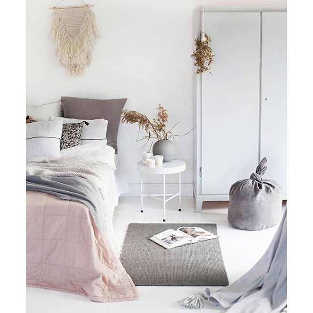 Beautiful bedroom design idea. White room with small grey rug, white wardrobe and small white bedside table