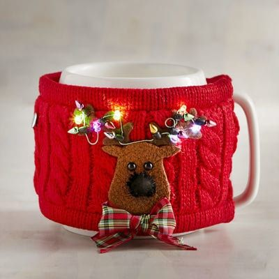When our festive reindeer sweater gives your mug a warm hug, watch his antlers light up with holiday cheer. The handcrafted cable knit sleeve attaches easily to the mug, making it a fun gift for your coffee buddy, officemate or Secret Santa.