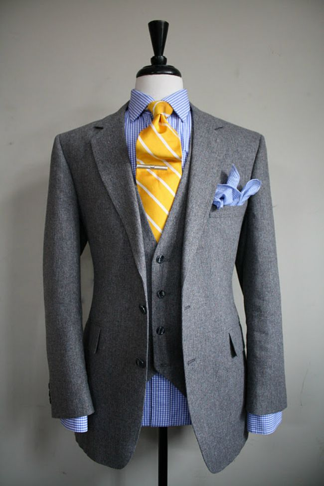 Single breasted gray wool suit with blue striped shirt and blue pocket square arranged as a blossoming bouquet. But going with a yellow tie? Delightful!