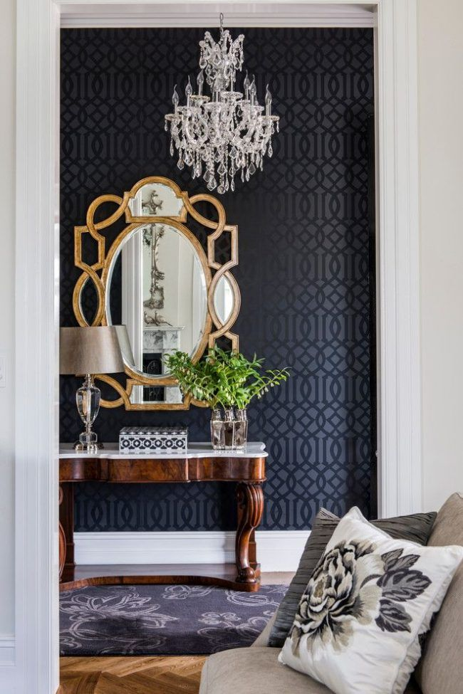 Английский стиль в гостиной: темные виниловые обои с орнаментом, деревянная лакированная мебель, хрустальная люстра в классическом стиле, настенное зеркало в оправе с эффектом состаривания и другие интерьерные элементы