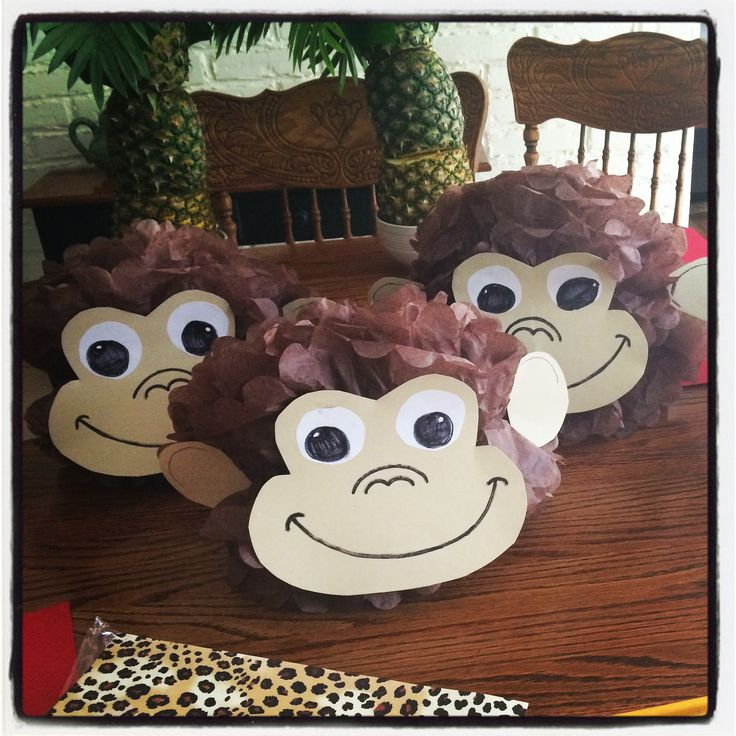 DIY monkey Pom poms. For curious George or jungle or monkey party. Brown Pom Pom with cut out monkey face taped on. Curious George party decoration ideas