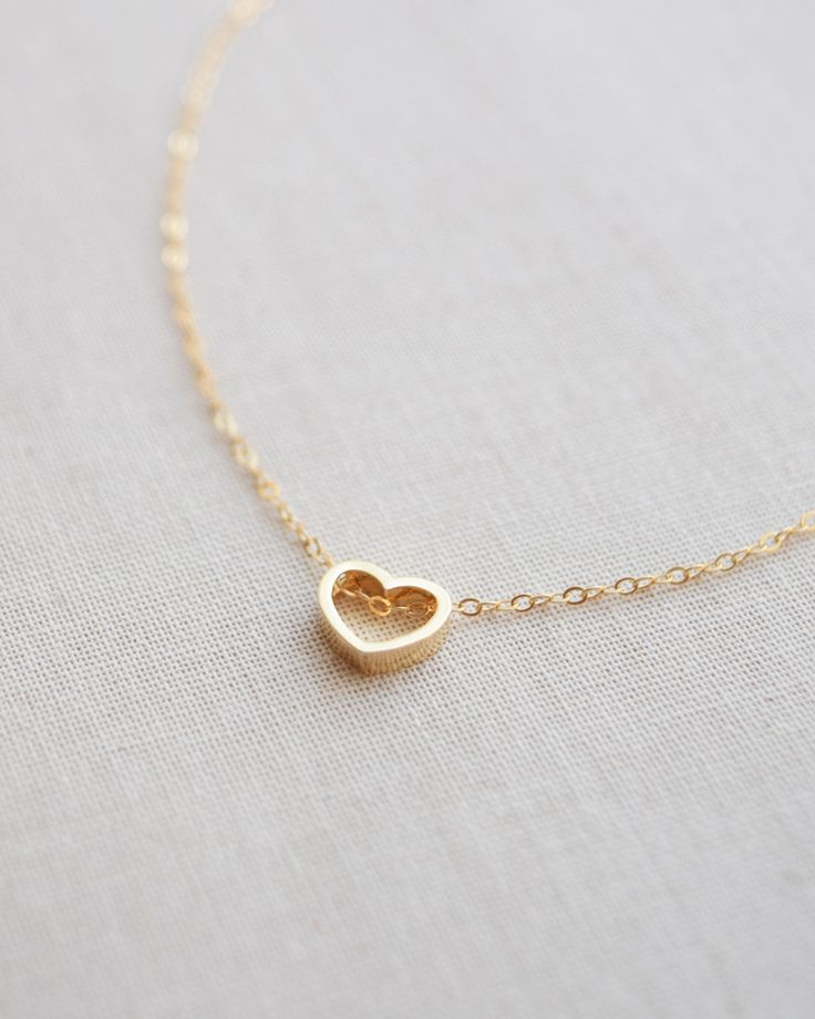 Sweet and simple gold heart outline necklace. The open heart necklace is great to layer with other necklaces and it matches anything! Heart charm measures approximately 3/8 inch in diameter. Letter ch