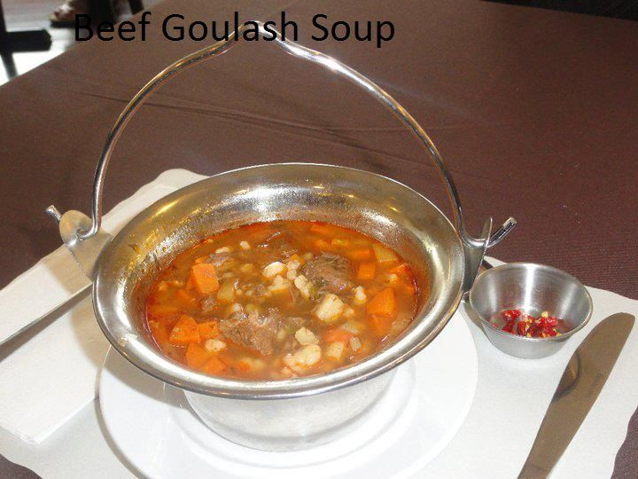 """Authentic Hungarian Goulash in Cauldren with beef chunks, potato, carrots, vegetables and home made """"pinched"""" pasta noodles: side of hungarian  very spicy paprika paste for those who prefer life in heat at Savoury and  Sweet Restaurant 3770 Bridgewater Street Niagara Falls Ontario"""