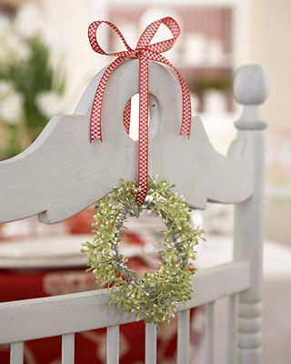 Mini-Wreaths made by inserting artificial flowers between twisted strands of silver pipe cleaners.