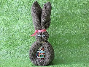 В данном мастер-классе мы с вами разберем, как сделать пасхального зайца из 'Киндер Сюрприза' и полотенца. Такой заяц будет отличным подарком на Пасху и принесет массу удовольствия вашим сластенам!Нам понадобится:- киндер-сюрприз;- полотенце 30*50 см;- атласная лента (для бантика);- глазки4- канцелярские резинки;- ножницы;- двухсторонний скотч;- обязательно — хорошее настроение.…
