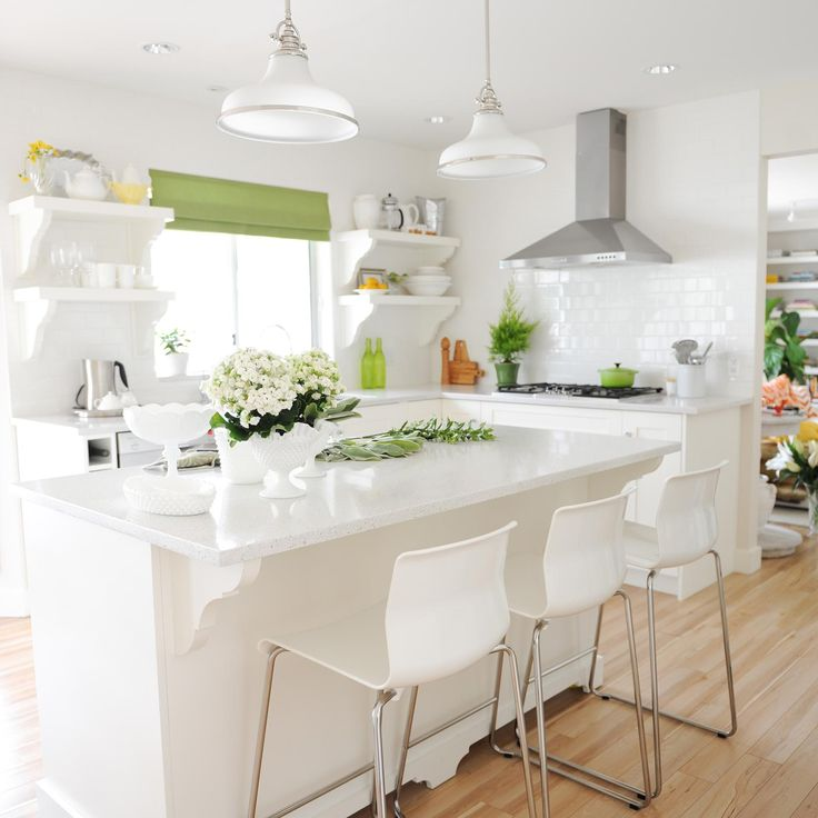 A white, bright kitchen with green curtains and accents