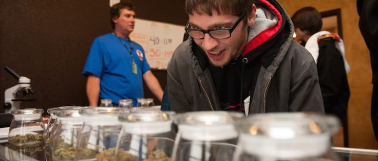 Tyler Williams of Blanchester, Ohio selects marijuana strains to purchase at the 3-D Denver Discrete Dispensary in Denver, Colorado. Legalization of recreational marijuana sales in the state went into effect at 8am this morning.