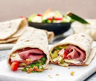 Lätta lunchen eller middag på språng. Rulla ihop en komplett måltid med hjälp av sallad, skivad rostbiff och krämig potatissallad i tunnbröd. Strössla med rostad lök och njut!