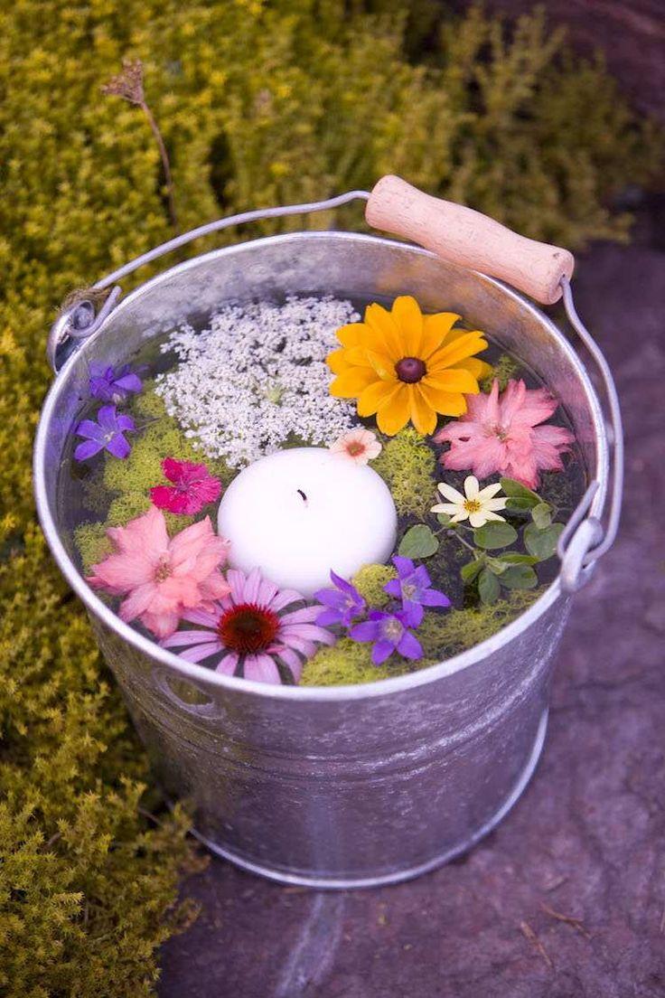 bougie d'extérieur flottantes dans un seau en zinc rempli de fleurs