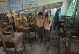 Students rescue tables and chairs from a flooded classroom in Kudus, Central Java, on Feb. 8, 2017. (Antara Photo/Yusuf Nugroho)