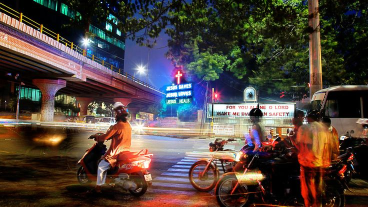 A photograph by photographer Niall O Cleirigh of a cross road in Chennai India, where Jesus saves, Jesis Loves, Jesus Heals is in neon signs... www.essentia.ie