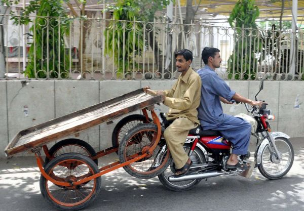 Two motorcyclists dangerously carry a push-cart pass through Mall road due to increase in transport fares in city, in Lahore on Tuesday, April 10, 2012.