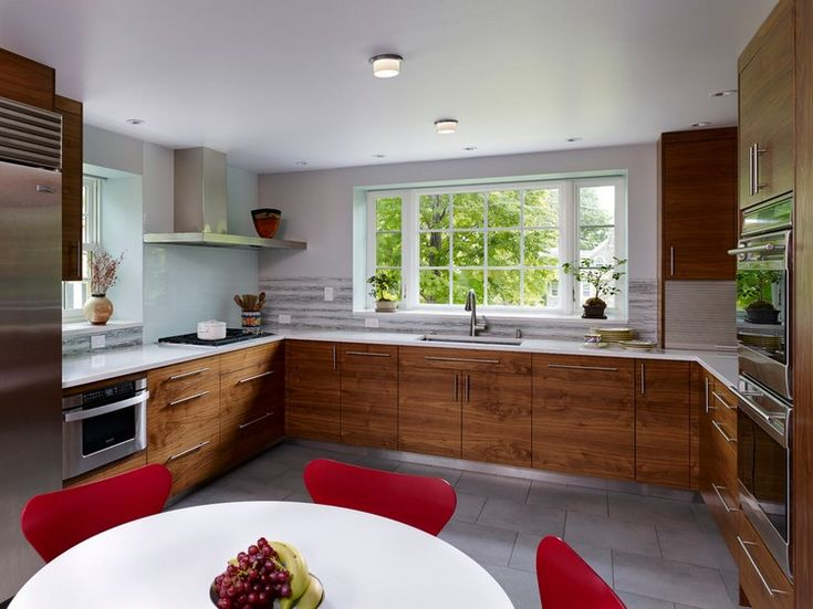 grande cuisine en U ouverte sur la salle à manger avec armoires en bois